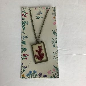 Necklace with red leaves in glass.